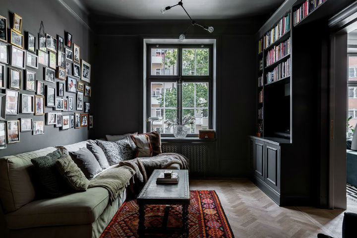 small living room with black walls and green sofa