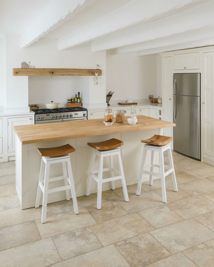 white kitchen with wooden table and  stools