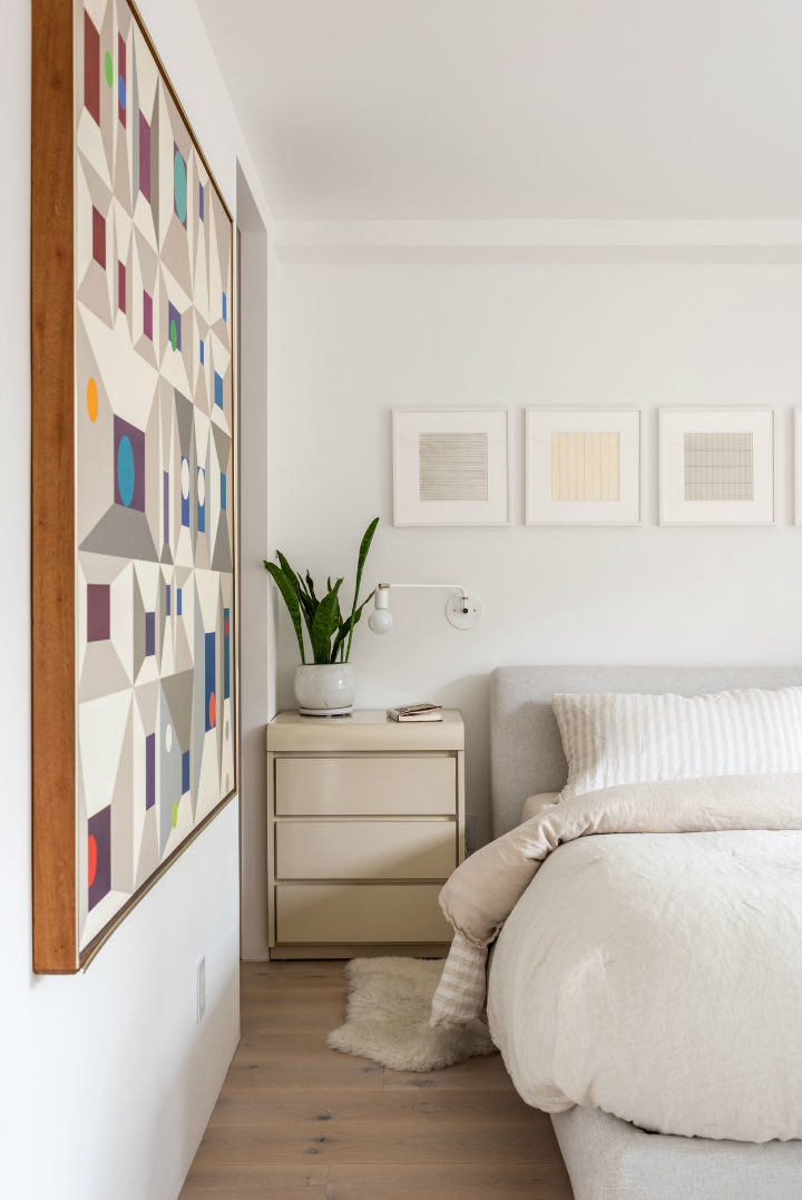 white bedroom with photo frames above
