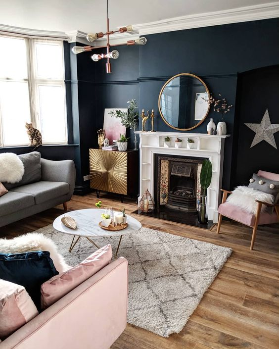 grey and pink sofas and a round shaped mirror