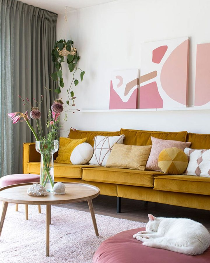 living-room with yellow velvet modern sofa and pink wall art