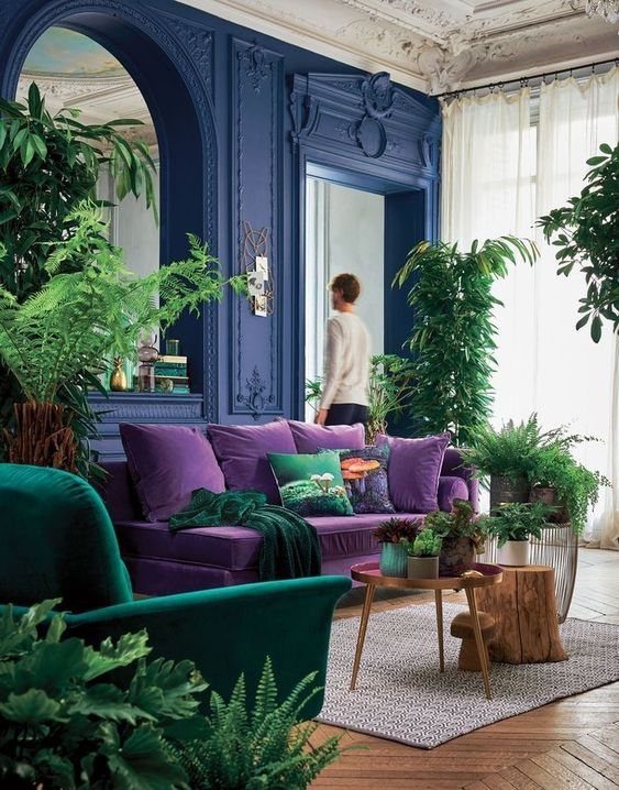 living room with bold velvet purse sofa and green armchair