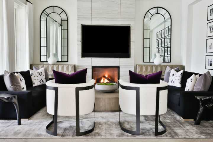 living room with black couches and white armchairs