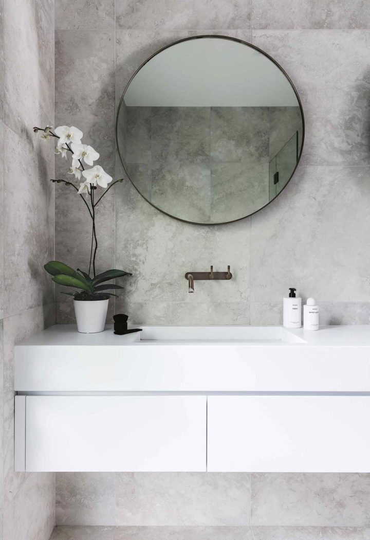 round shaped mirror and indoor plant in bathroom