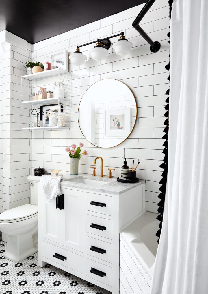 small black and white bathroom with round mirror and open shelves