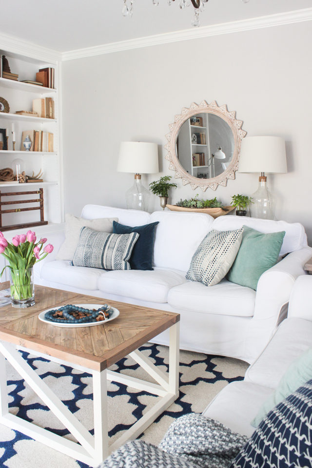 small white living room with navy and aqua blue pillows