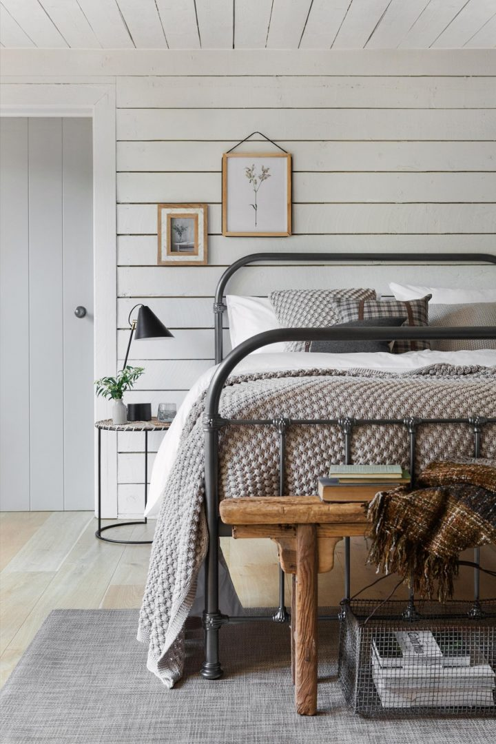 contemporary country white bedroom with black iron bed and wood flooring