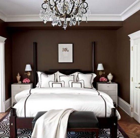 bedroom with dark brown walls and chandelier