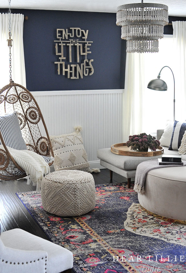 contemporary living room with hanging rattan chair black wall