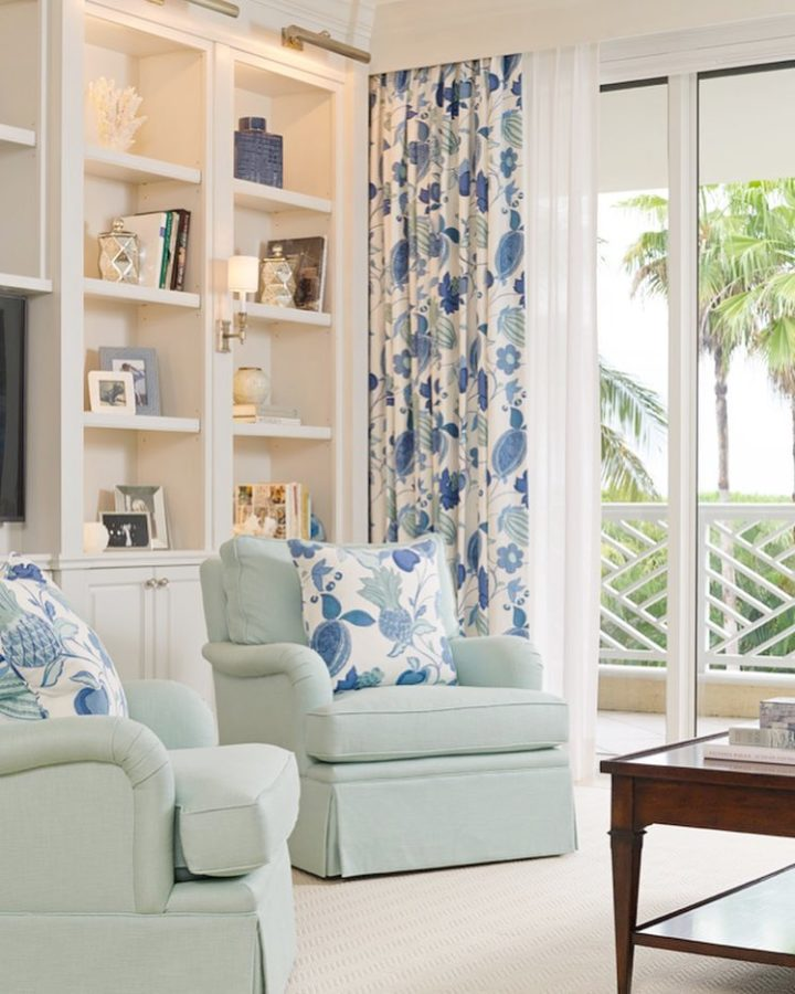 light blue armchairs and blue and white pillows and curtains
