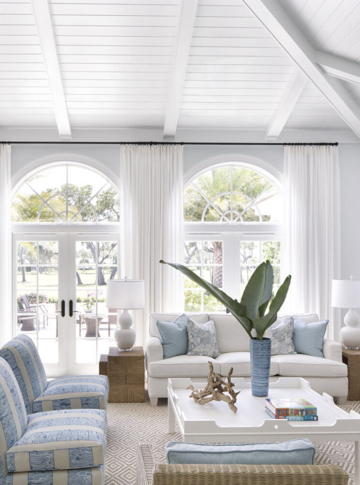white windows and curtains and light blue striped armchairs and a white sofa