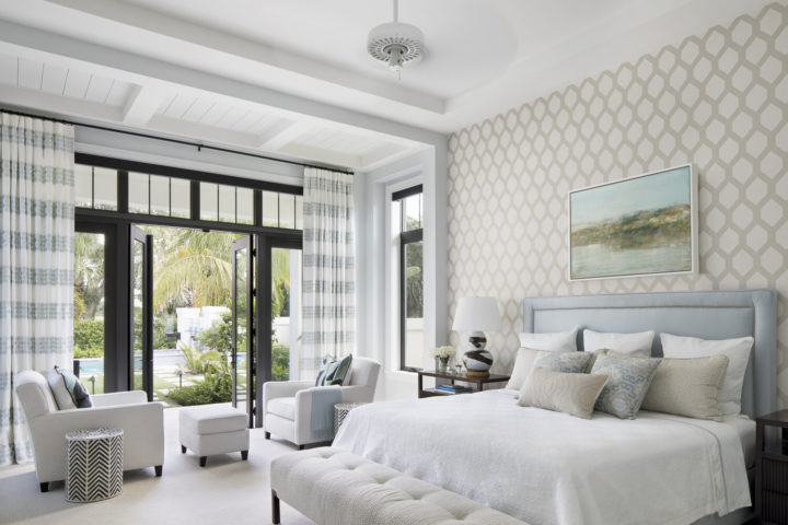 white bedroom with patterned wall and striped curtains