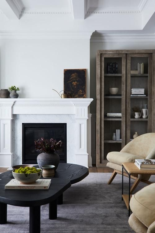 white fireplace with few decoartive items on the mantel and a table nearby
