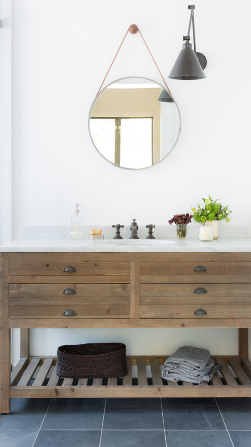 round mirror on the wall as part of a bathroom vanity