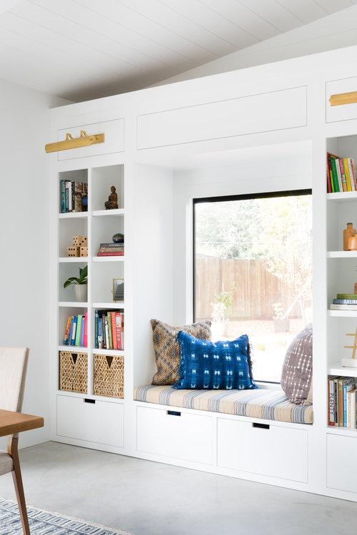 white window bench with bookshelf all around