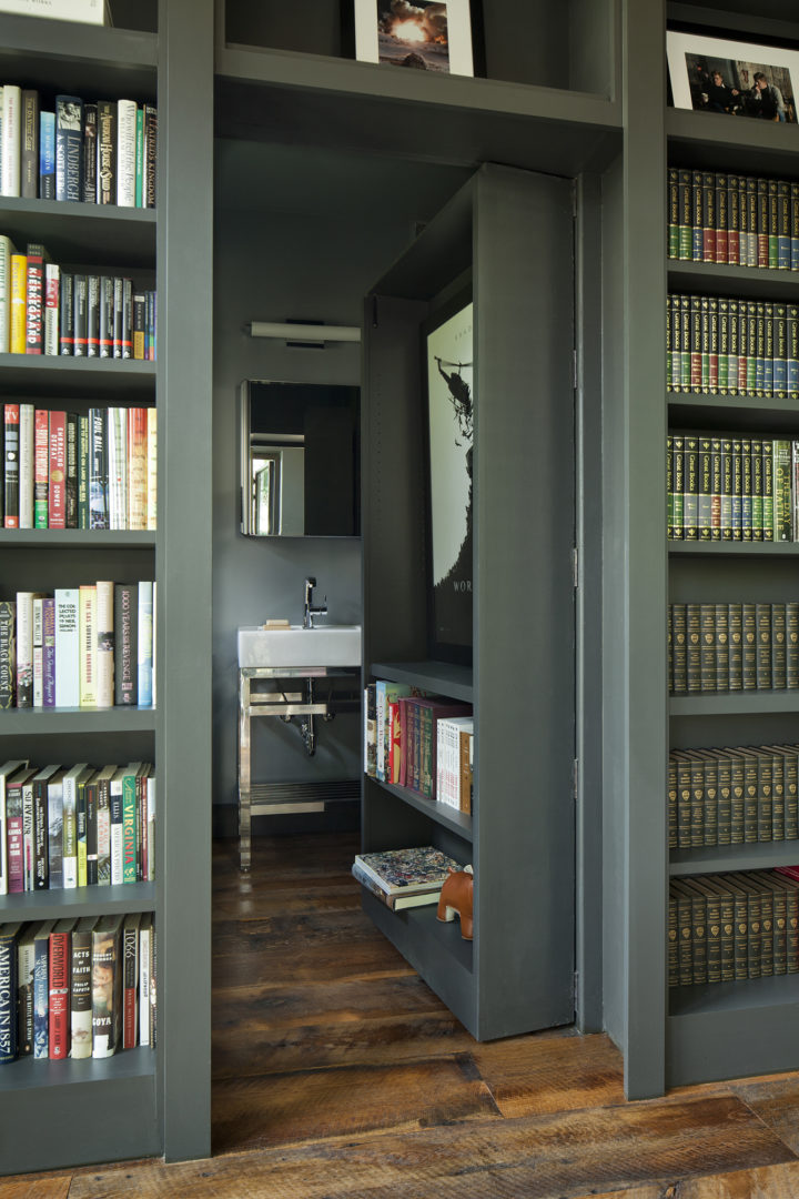 big bookcase with many books and a secret bathroom behind it