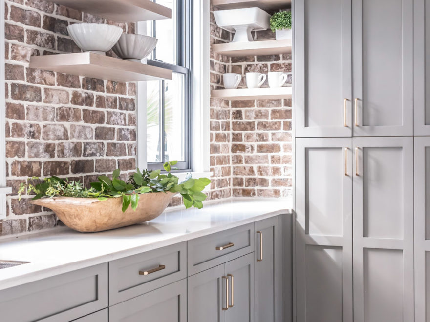 dove gray kitchen cabinets with brick wall