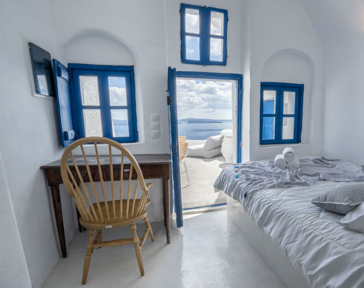Canvas Suites Santorini Greece bedroom  with blue windows