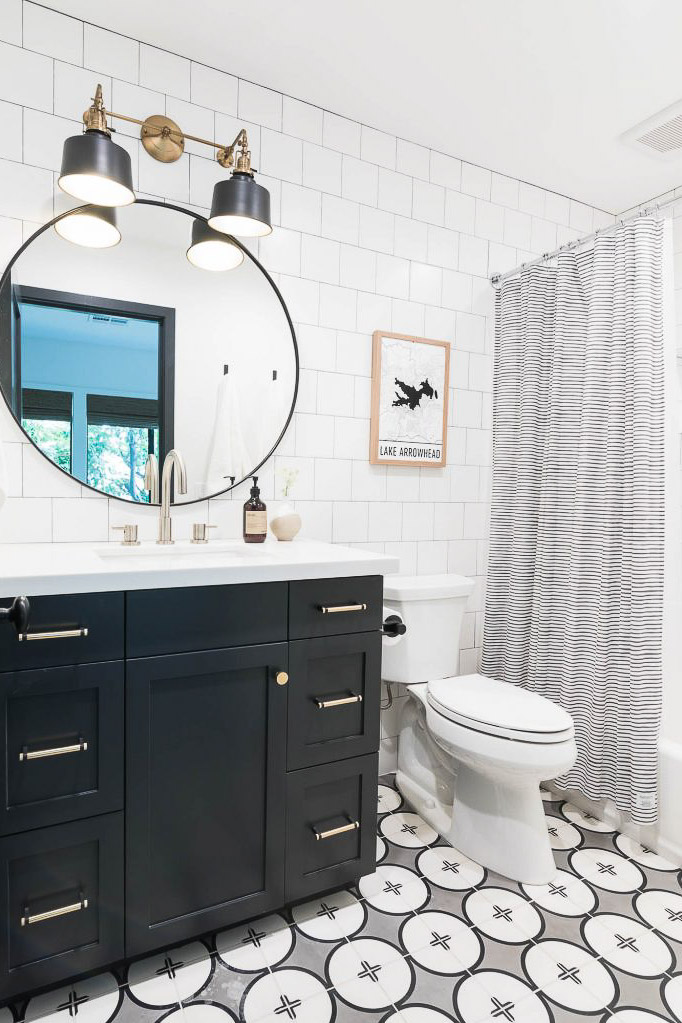 blak and white bathroom with black vanity and large round mirror