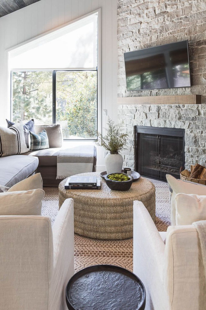 cozy modern country small living room with stone fireplace with TV above