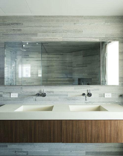 minimalist bathroom with grey tiles double sink and wood vanity