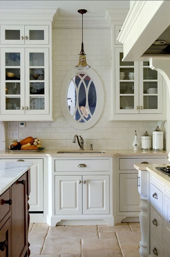 white country kitchen with oval mirror above the sink