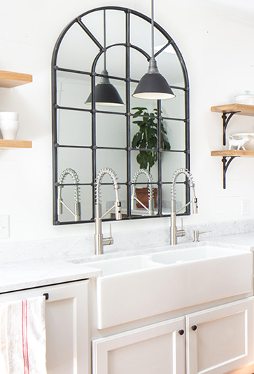 black metal lattice mirror above kitchen sink to simulate a window