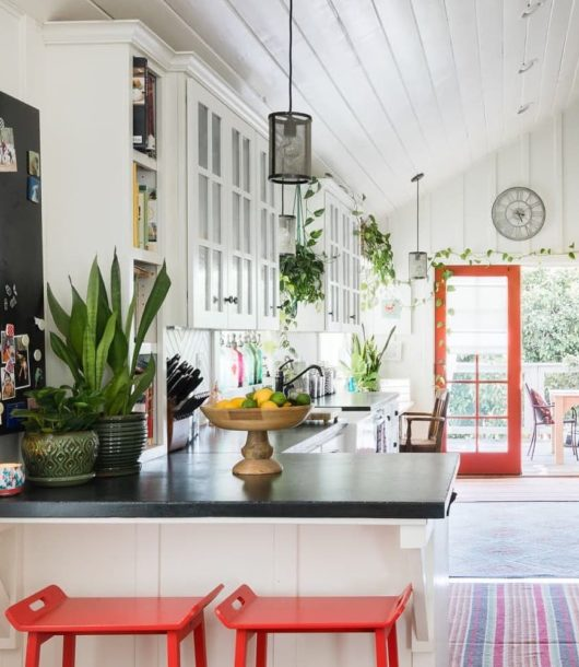 summer farmhouse-style kitchen with red stools and red door