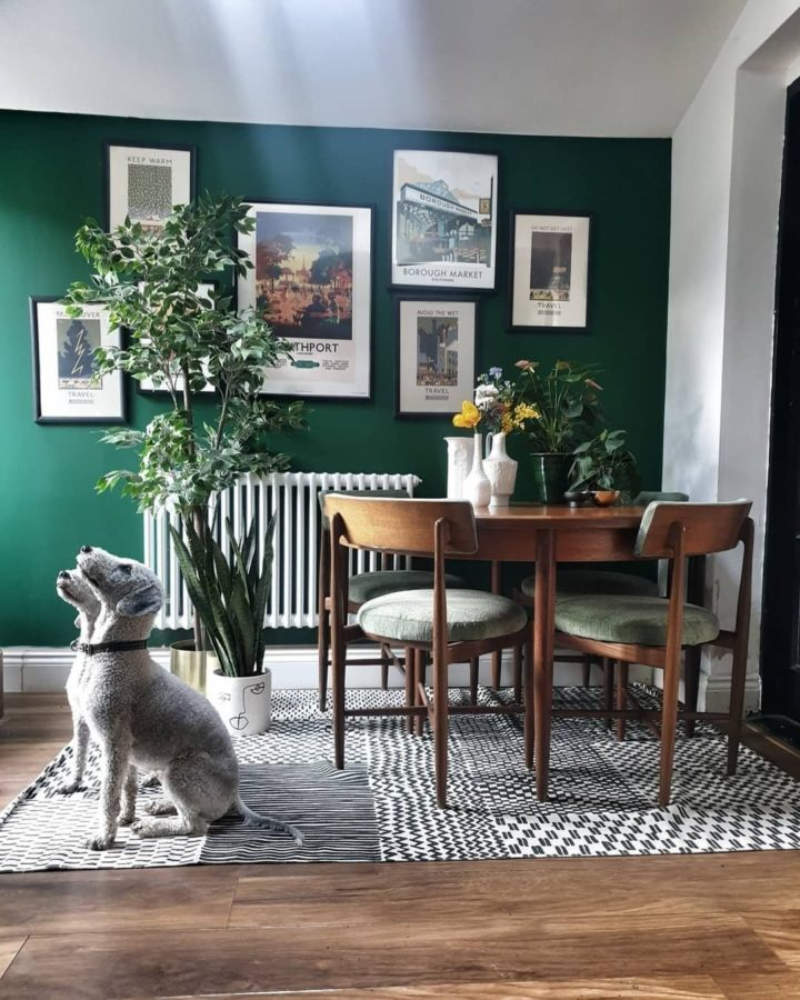 small dining room with emerald green wall and art gallery