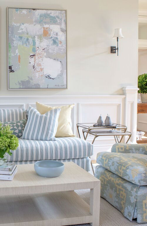 timeless living room with white and light blue striped sofa and yellow pillows