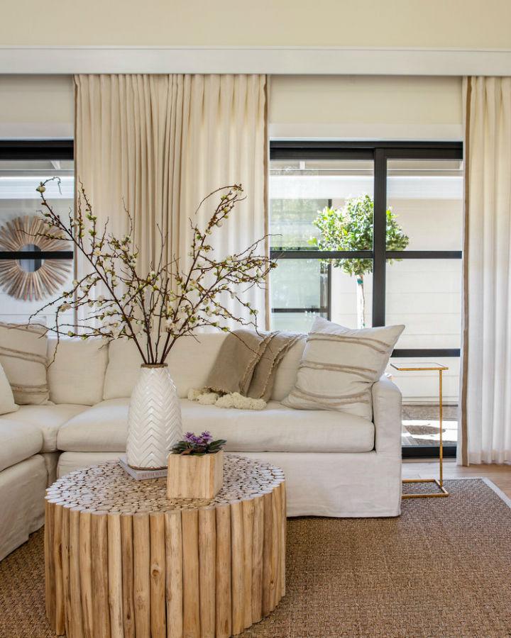 ruang tamu berwarna krem abadi dengan meja kopi kayu bulat