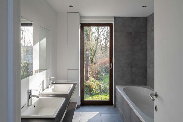 white with grey simple contemporary bathroom with glass door to outdoor and double sinks