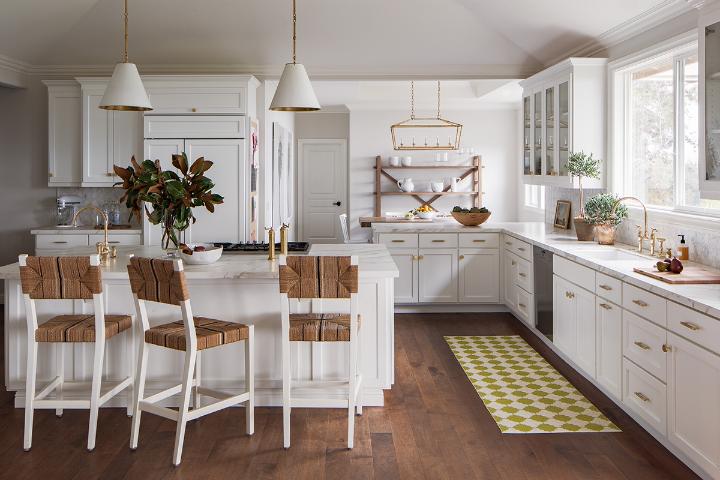 cozinha branca com ilha e bancos de madeira