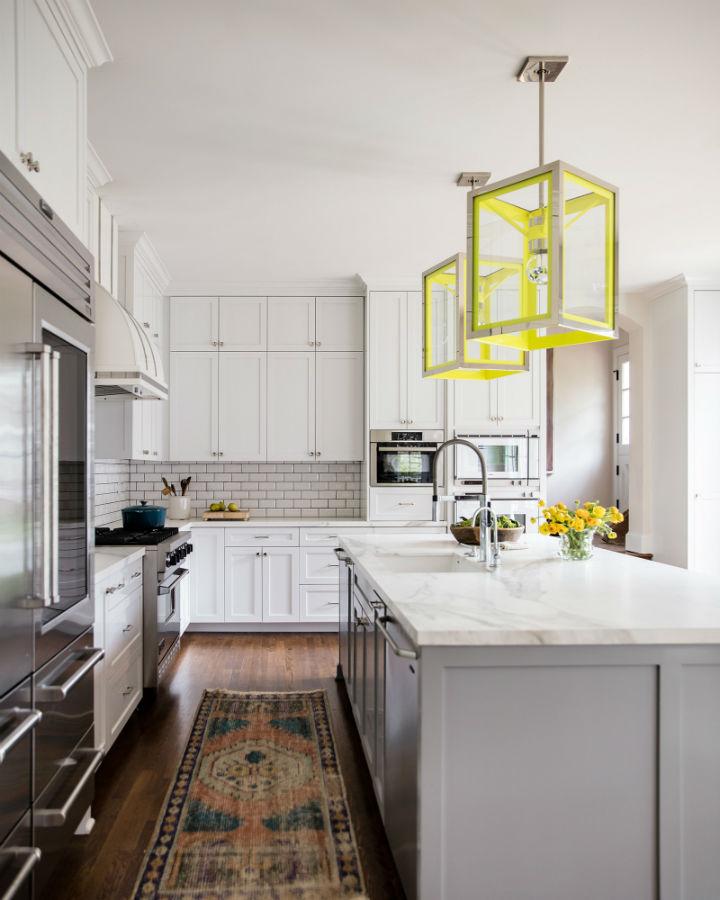 cozinha cinza e branca com luzes amarelas de ilha e gripe