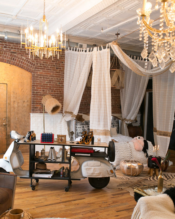 loft bedroom with bed canopy curtain and brick walls