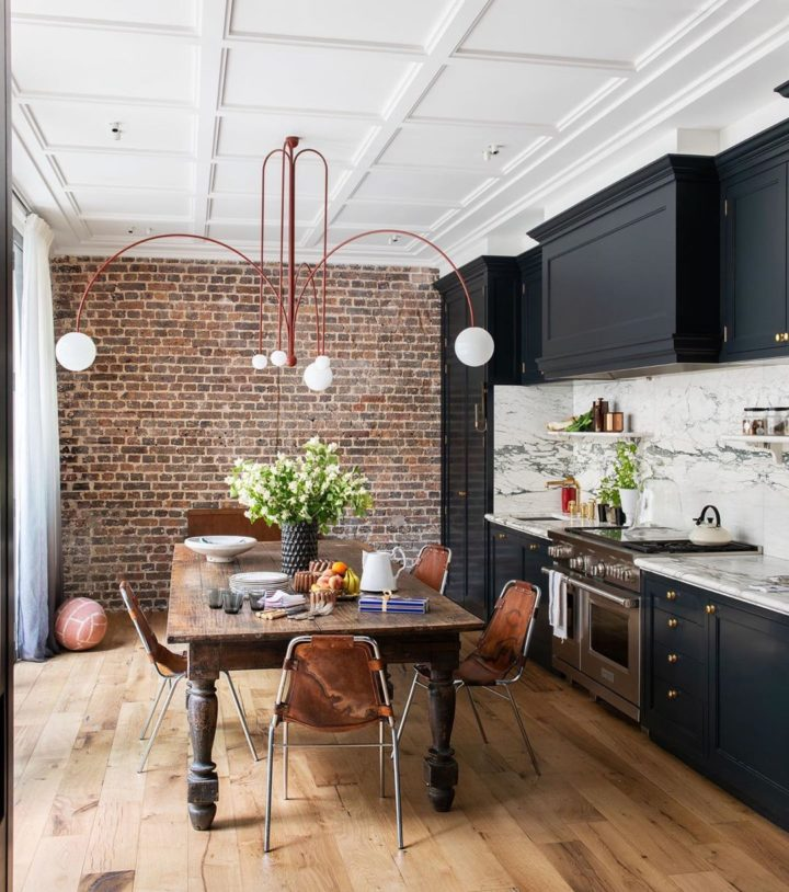 black and white kitchen with vintage wood table and brick wall