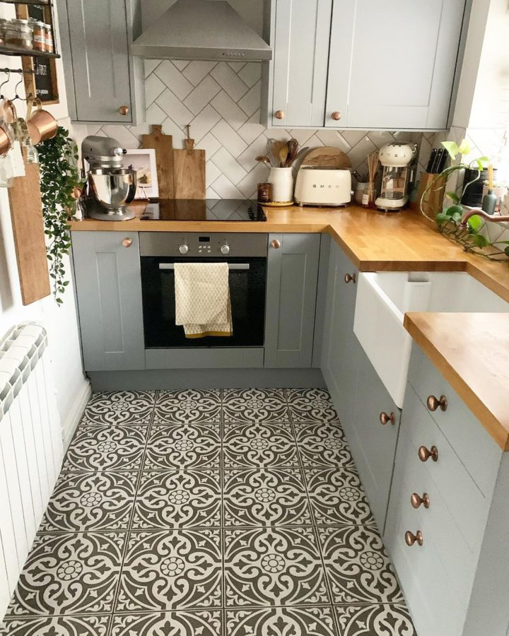 small modern country kitchen with grey cabinets wood worktop and black and white retro floor tiles