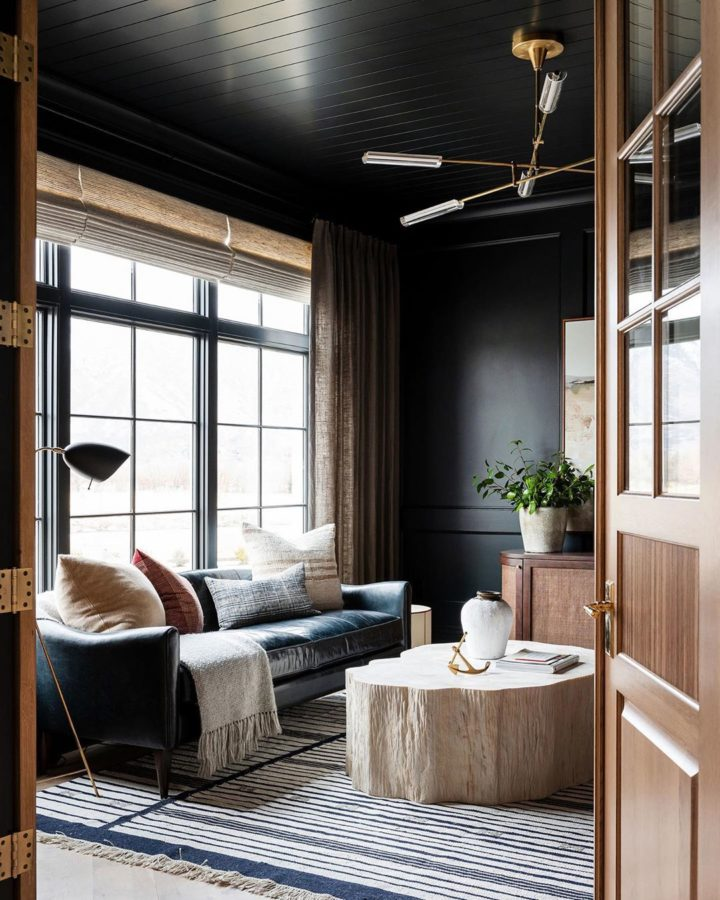 small living room with black walls, large striped rug and leather sofa