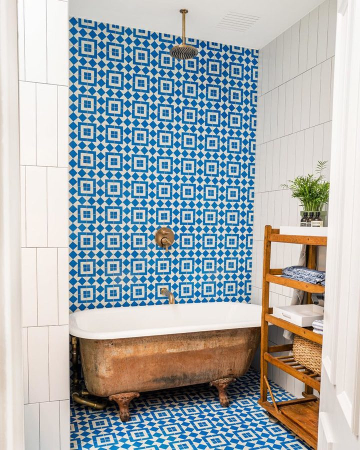 bathroom with blue and white Moroccan tiles and copper freestanding bathtub