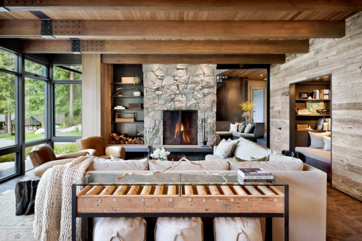 rustic large living room with stone fireplace and large windows