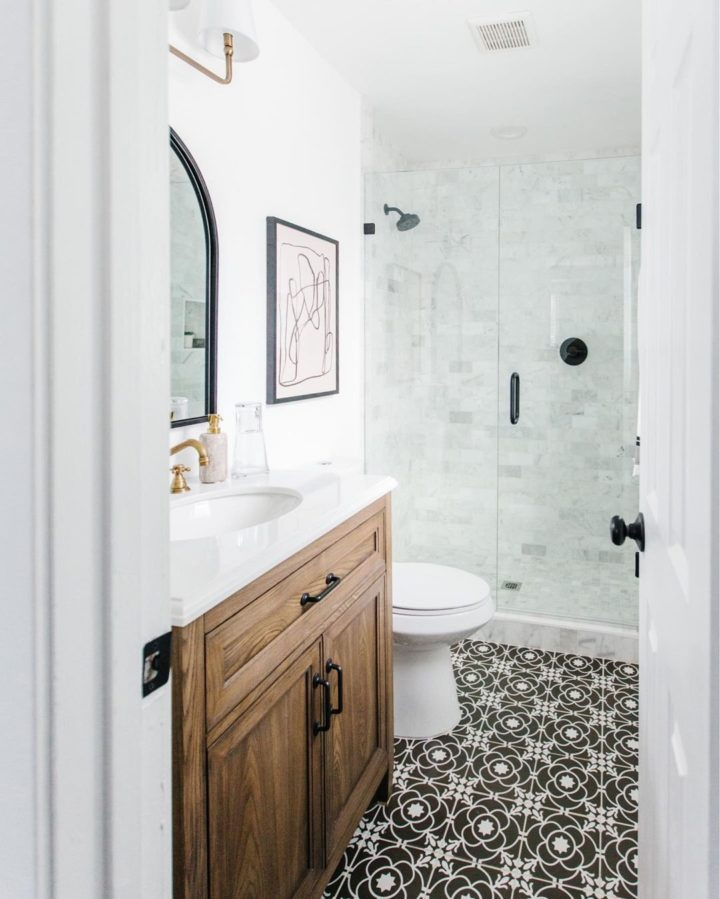 bathroom with white tiles and black and white stencilled flooring tiles