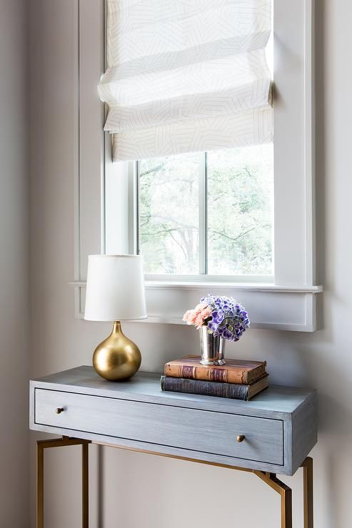 dark and gold console table under window