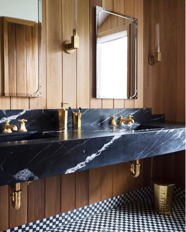 bathroom with luxury marble vanity and gold hardware wood paneling and black and white flooring
