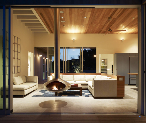 modern living room with central fireplace by CCS Architecture